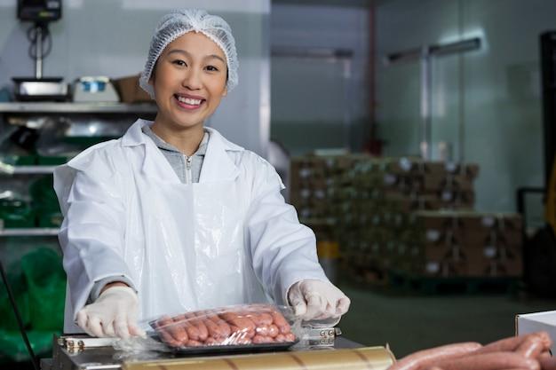 Açougueiro embalagem salsichas cruas