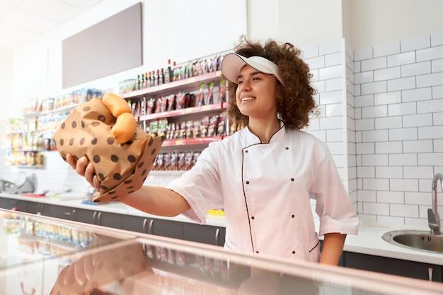Açougueiro feminino dando salsichas no balcão.