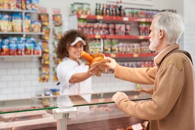 Açougueiro feminino dando salsichas para homem idoso.