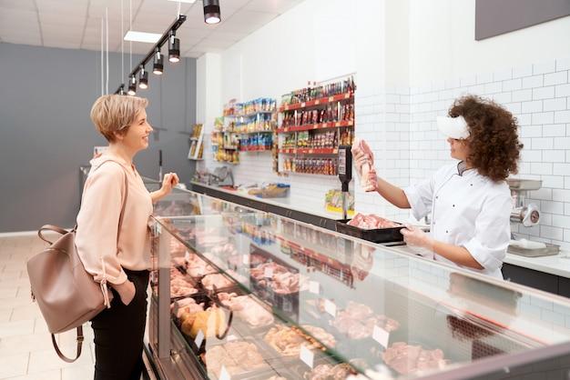 Açougueiro feminino demonstrando carne para mulher.