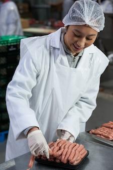 Açougueiro feminino embalagem salsichas cruas
