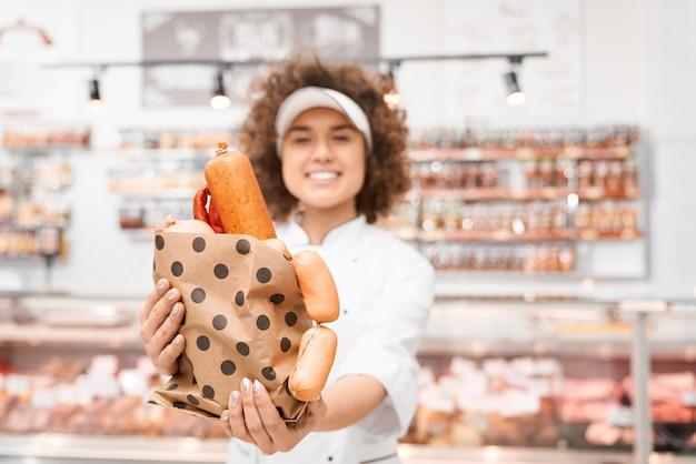 Açougueiro feminino segurando o saco com salsichas.