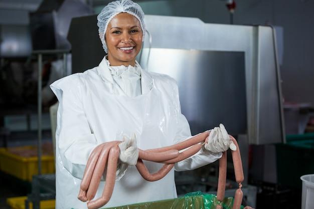 Açougueiro feminino segurando salsichas