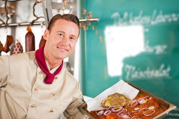 Açougueiro inteligente mostrando deliciosa refeição servida na bandeja