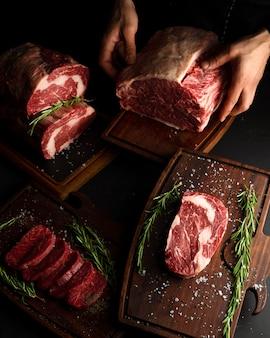 Açougueiro mostrando diferentes cortes de carne crua.