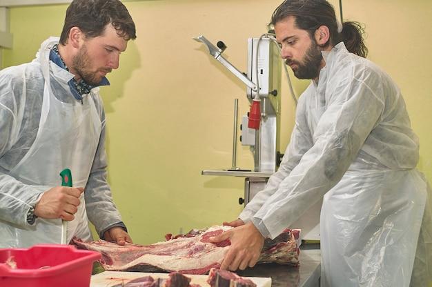 Açougueiro no trabalho prepara os cortes de carne no balcão e com as ferramentas do ofício