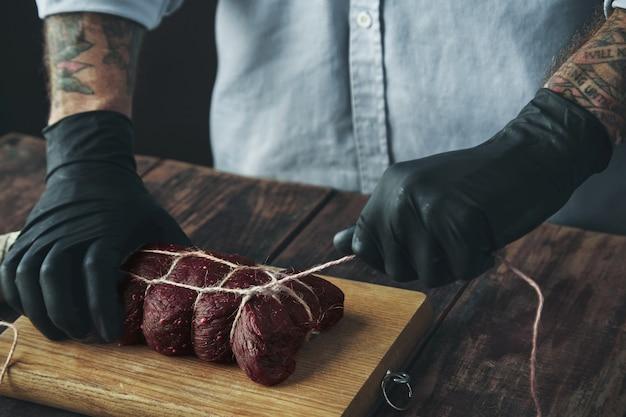 Açougueiro tatuado irreconhecível em luvas pretas amarra um pedaço de carne com uma corda artesanal para fumá-la na madeira