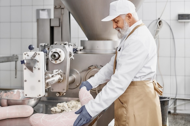 Açougueiro, trabalhando com a produção de salsichas na fábrica.