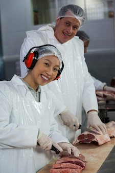 Açougues cortando carne na fábrica de carne