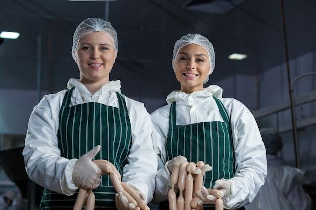 Açougues fêmeas processando salsichas