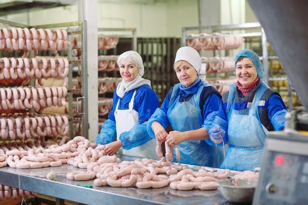Açougues processando salsichas na fábrica de carne.