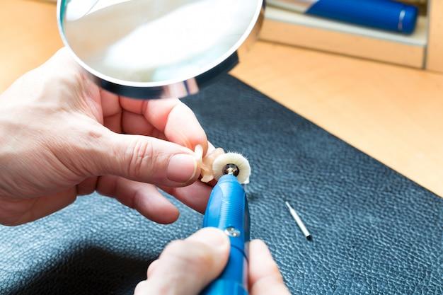 Acoustician trabalhando em um aparelho auditivo