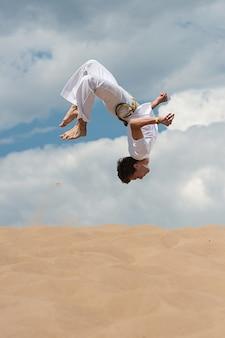 Acrobat realiza um truque acrobático, dar cambalhotas na praia
