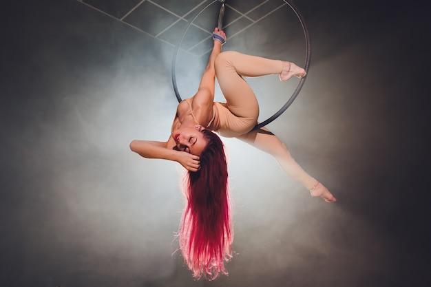 Acrobata aérea no ringue. uma jovem executa os elementos acrobáticos no anel de ar.