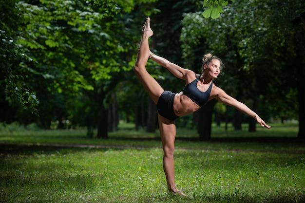 Acrobata de menina de esportes realiza elemento acrobático na grama