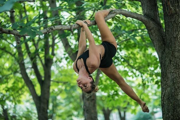 Acrobata de menina executa elemento acrobático na árvore.