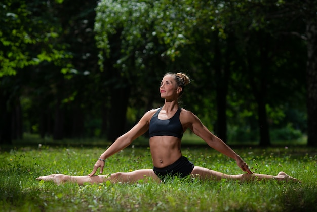 Acrobata de menina realiza elemento acrobático na grama do parque