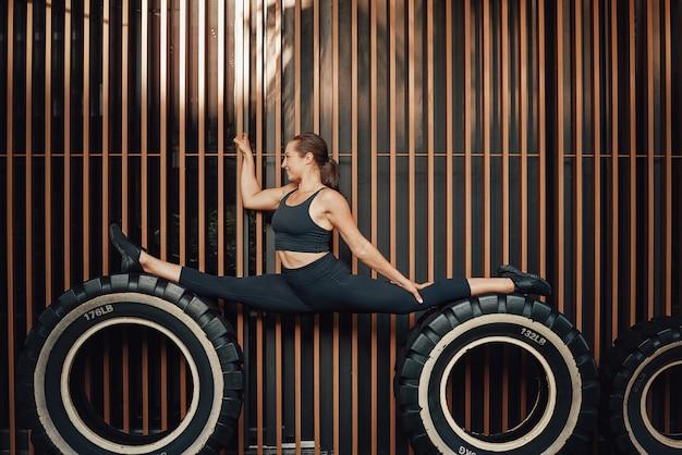 Acrobata feminina flexível posa no fundo da parede, ficando sobre rodas enormes. mulher alegre e estilo de vida esportivo.