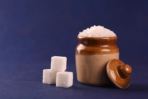 Açúcar. açúcar granulado branco e açúcar refinado em um fundo azul