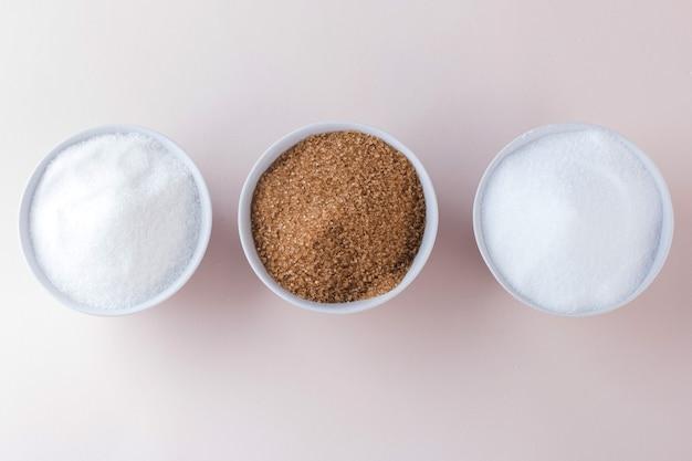 Açúcar branco, açúcar de cana e substituto do açúcar na vista superior das tigelas.