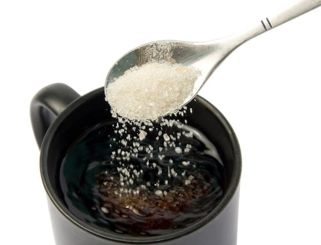 Açúcar branco caindo da colher em um copo isolado no fundo branco