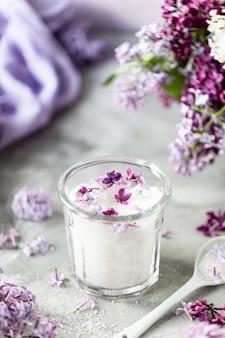 Açúcar branco com flores lilás em um fundo de mármore.