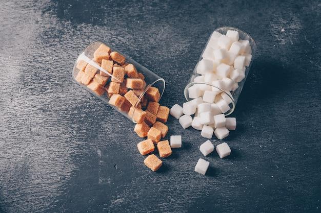 Açúcar branco e marrom em copos de água. vista de alto ângulo.