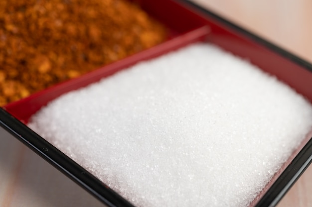 Açúcar branco em um copo no chão de madeira.