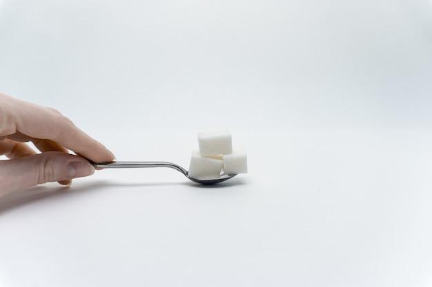 Açúcar branco em uma colher de chá sobre um fundo claro e uma mão feminina