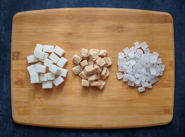 Açúcar branco, marrom e pirulito em uma placa de madeira