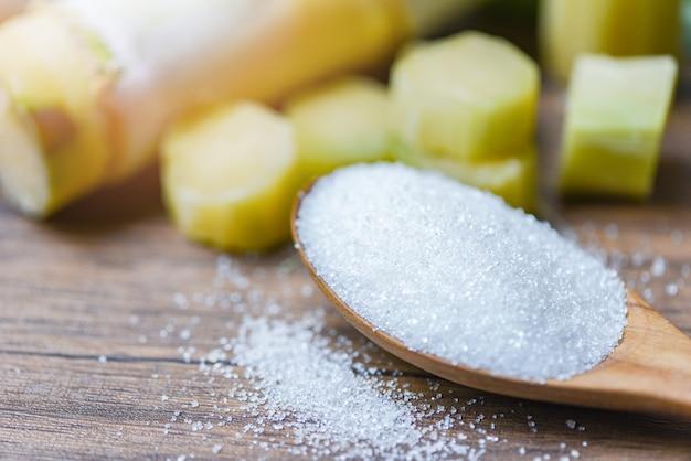Açúcar branco na colher de pau e cana-de-açúcar na mesa de madeira