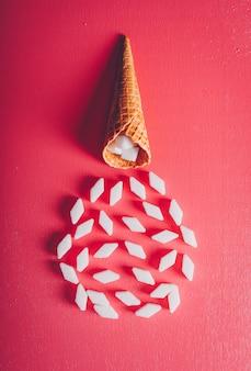 Açúcar branco no waffle de sorvete em uma mesa vermelha e rosa. vista do topo.