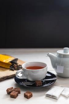 Açúcar castanho perto de xícara de chá