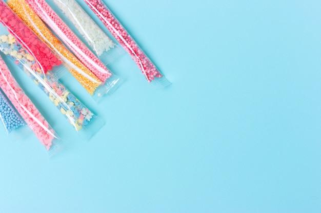 Açúcar colorido polvilha no pacote em background azul