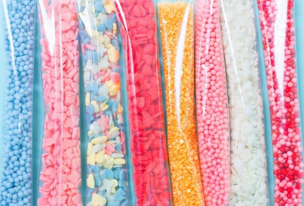 Açúcar colorido polvilha no pacote em fundo azul