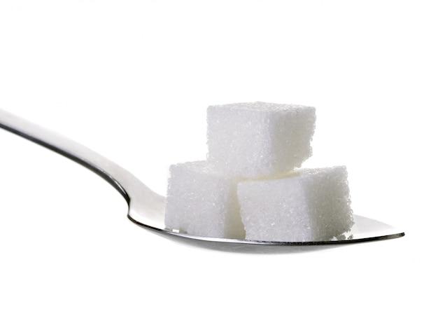 Açúcar cubo em colher de chá, isolado no fundo branco