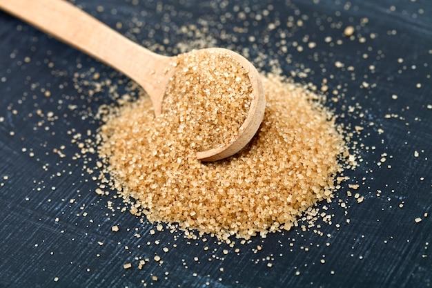 Açúcar de bastão de brown na colher de madeira na placa preta.