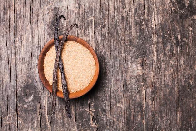Açúcar de baunilha em uma tigela de madeira sobre um fundo rústico. duas vagens de baunilha com açúcar mascavo