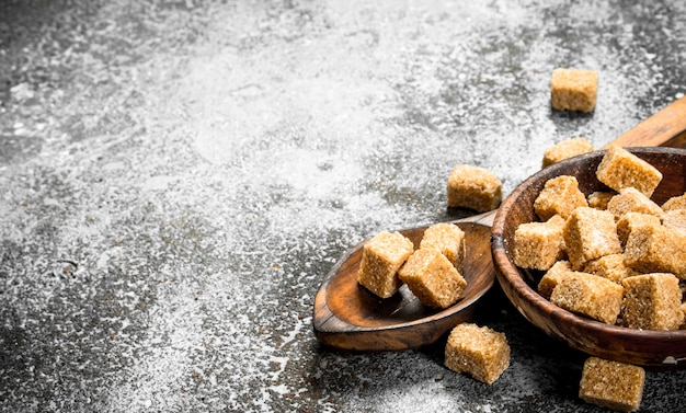 Açúcar de cana em uma tigela. sobre um fundo rústico.