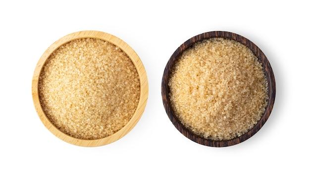 Açúcar de cana marrom em uma tigela de madeira, isolado no fundo branco. vista do topo