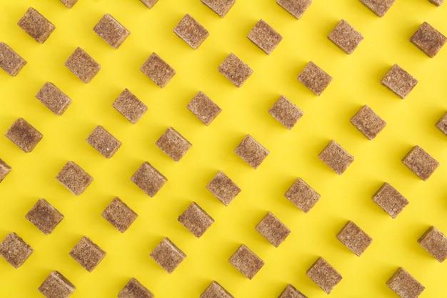 Açúcar de cana no fundo amarelo. vista superior. plano plano.