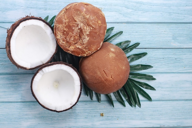 Açúcar de palma ou coco com metade de coco e folhas em fundo de madeira