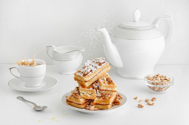 Açúcar em pó está derramando em bolachas vienenses com nozes e espirrando café na mesa do café