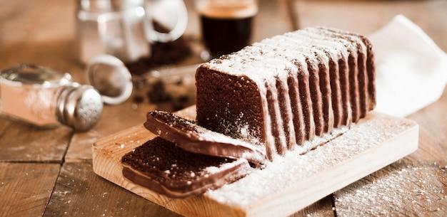Açúcar em pó na fatia de bolo sobre a tábua de cortar