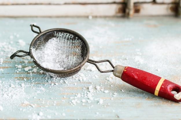 Açúcar em pó na peneira vintage