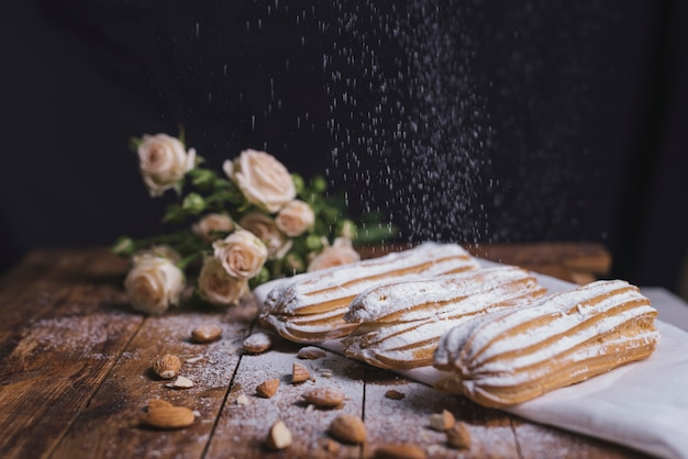 Açúcar em pó, polvilhado em eclairs cozido com amêndoas em pano de fundo de madeira