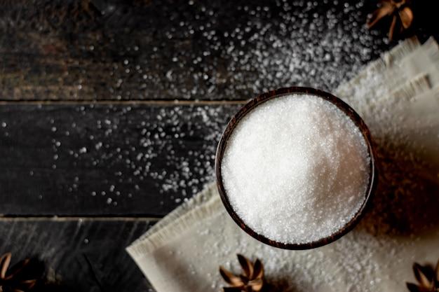 Açúcar em um copo e colher em uma mesa preta.