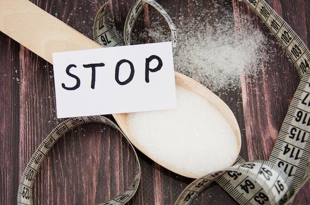 Açúcar em uma colher de pau e a palavra pare no adesivo conceito de dieta ou diabetes