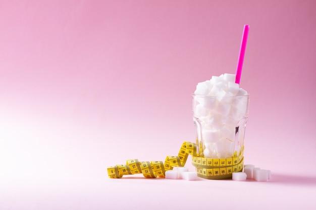 Açúcar em vidro com fita métrica em fundo rosa com espaço de cópia