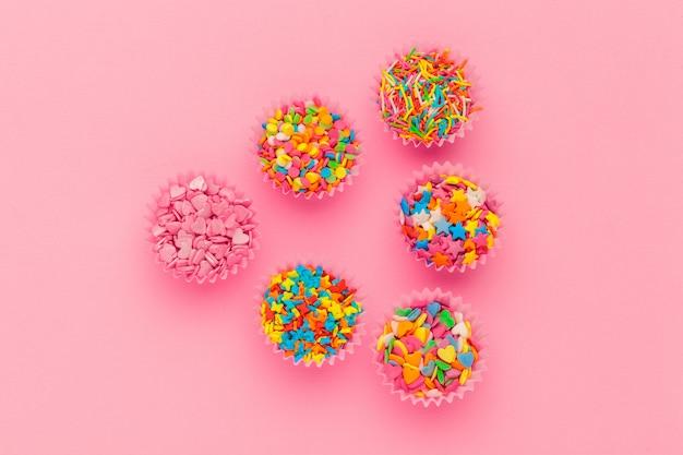 Açúcar granulado, decoração para bolo e sorvete e biscoitos em rosa